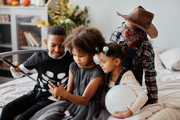 Gruppe afroamerikanischer kinder, die zu hause halloween-kostüme tragen und smartphone verwenden