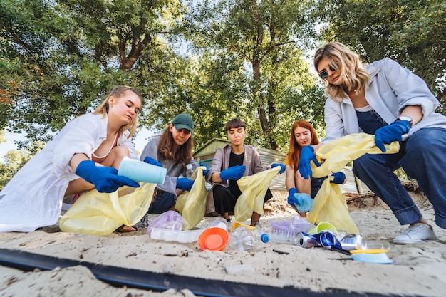 Gruppe aktivistenfreunde, die plastikabfall auf dem strand sammeln. umweltschutz.