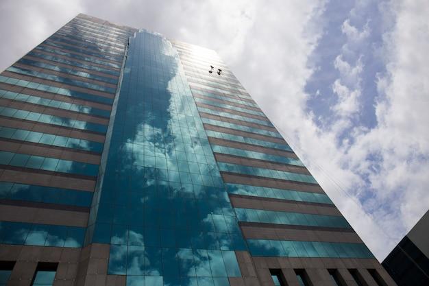 Gruppe arbeitskräfte, die windows-service auf hohem aufstiegsgebäude säubern