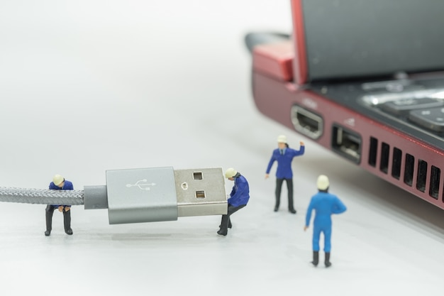Gruppe arbeitskraftminiaturzahlen, die an usb-kabel mit laptop-computer arbeiten