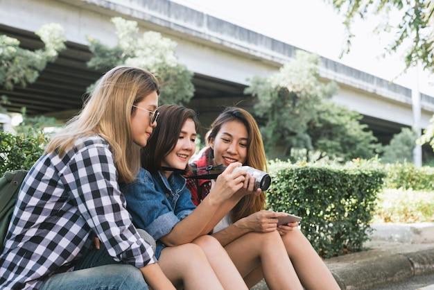 Gruppe asiatinnen, die zusammen sitzen und das schauen des fotos beim reisen park betrachten