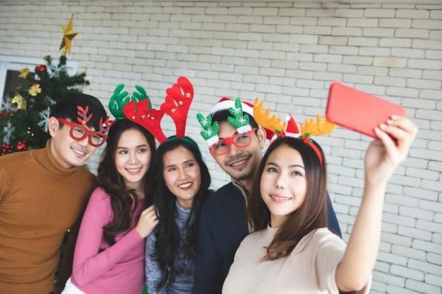 Gruppe asiatische freunde, die zu hause selfie mit freund durch smartphone während der weihnachtsabend-partei oder des neuen jahres nehmen, feiern partei. happy winter xmas und happy new year party-konzept