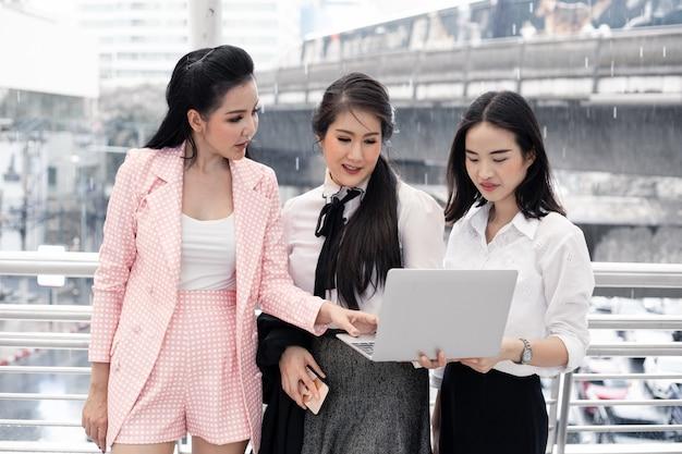 Gruppe asiatische geschäftsfrauen besprechen die arbeit, die auf informationen vom computer basiert