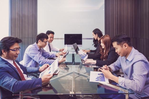 Gruppe asiatische geschäftsleute in der zufälligen klagenfunktion und -sitzung