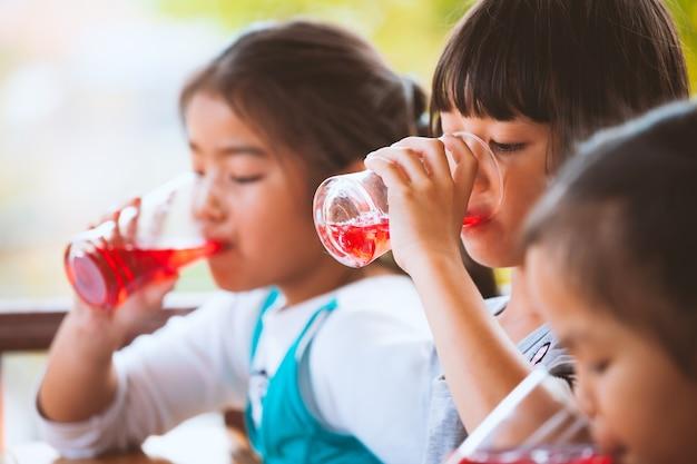 Gruppe asiatische kinder, die zusammen rotes saftwasser mit eis vom glas trinken