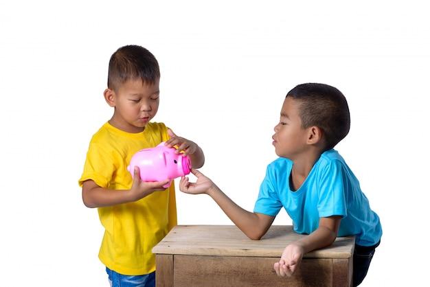 Gruppe asiatische kinder haben spaß mit dem sparschwein, das auf weiß lokalisiert wird