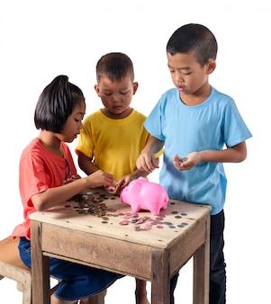 Gruppe asiatische kinder helfen, die münzen in das sparschwein zu setzen, das auf weißem hintergrund lokalisiert wird