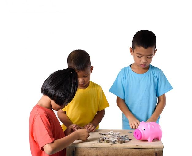 Gruppe asiatische kinder helfen, münzen in das sparschwein zu setzen, das auf weißen hintergrund lokalisiert wird