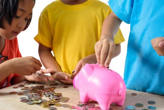 Gruppe asiatische kinder helfen, münzen in sparschwein zu setzen