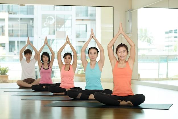Gruppe asiatische leute, die yoga-innenklasse in namaste haltung ausbilden