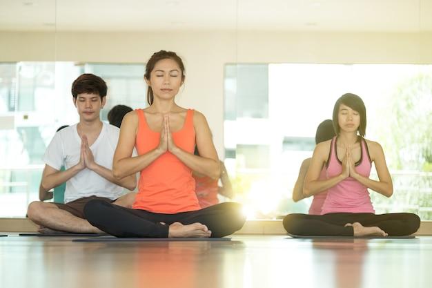 Gruppe asiatische leute, die yogahallenklasse in namaste lage mit freudigem ausbilden, entspannen sich und meditieren gefühl, wellness, wohl und gesundes lebensstilkonzept