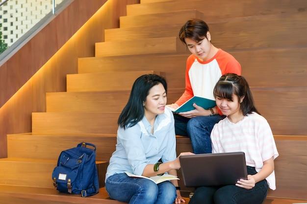 Gruppe asiatische studenten, die notebookunterrichtsunterricht mit ihrem lektor beim sitzen auf bibliothekstreppenhintergrund verwenden