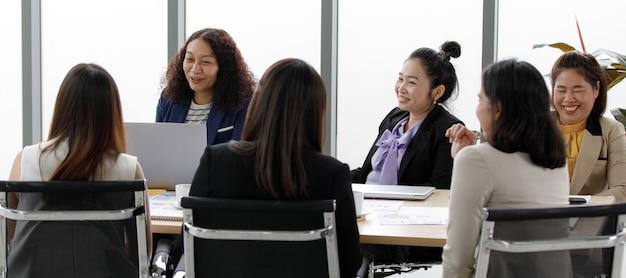 Gruppe asiatischer, erwachsener, weiblicher geschäftsfrauen in formellen anzug, die lächelnd auf den großen bildschirm grüßen, grüßen multikulturelle kollegen in telefonkonferenzen.
