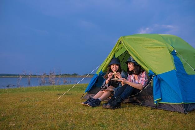 Gruppe asiatischer freunde, die im sommer zusammen mit dem glück gitarre trinken und gitarre spielen, während sie bei sonnenuntergang in der nähe des sees campen?