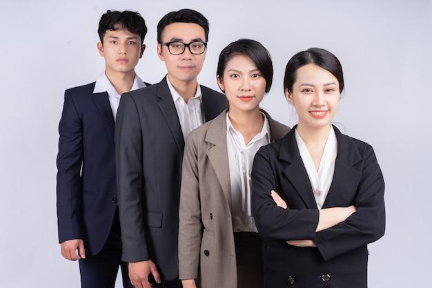Gruppe asiatischer geschäftsleute, die auf einem weißen hintergrund posieren
