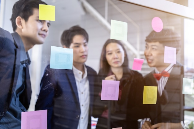 Gruppe asiatischer geschäftsleute mit unterschiedlichen geschlechtern (lgbt) abstrakte unschärfe mit fokus verwenden post-it-notizen, um ideen zu teilen. brainstorming-konzept. haftnotiz an der glaswand im besprechungsraum im büro