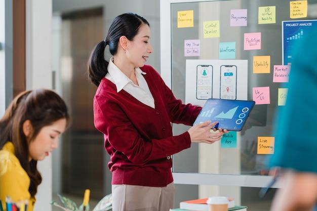 Gruppe asiatischer junger kreativer leute, die brainstorming-ideen treffen, die geschäftspräsentationsideen-kollegen des entwurfsprojekts der mobilen anwendungssoftware im modernen büro durchführen. teamwork-konzept für mitarbeiter