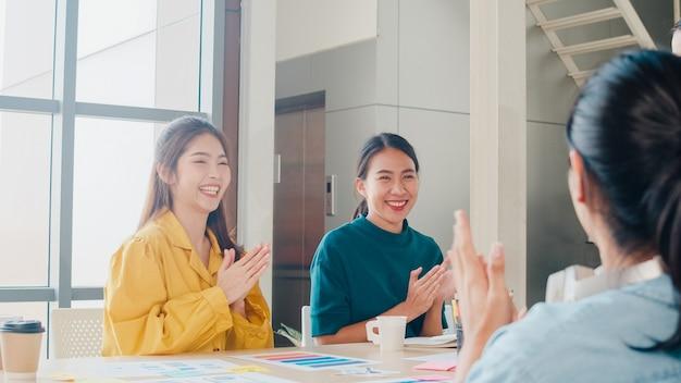 Gruppe asiatischer junger kreativer leute in der intelligenten freizeitkleidung, die das geschäft bespricht, feiern das geben von fünf, nachdem sie sich glücklich gefühlt und einen vertrag oder eine vereinbarung im amt unterzeichnet haben. teamwork-konzept für mitarbeiter.