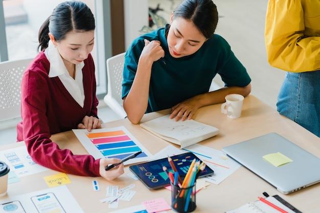 Gruppe asiatischer junger kreativer leute japanischer weiblicher chefaufseher, der praktikant oder neues mitarbeiter hispanisches mädchen unterrichtet, das bei der schwierigen aufgabe im modernen büro hilft. teamwork-konzept für mitarbeiter.