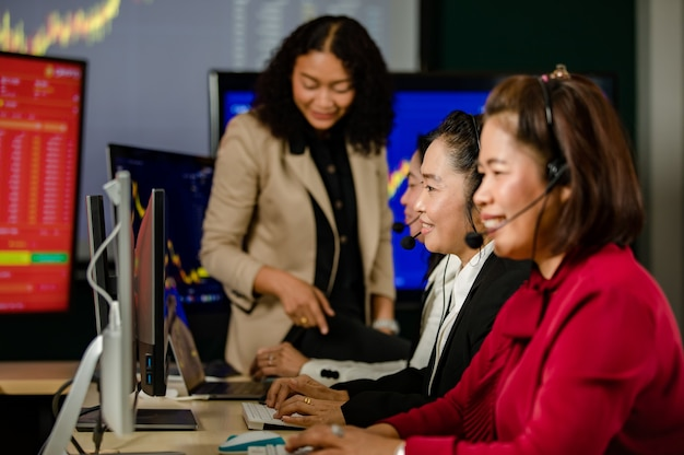 Gruppe asiatischer kundendienstmitarbeiterinnen trägt mikrofon-headsets, die lächelnd vor dem täglichen grafikdiagramm-computerbildschirm sitzen, sprechen und handeln kaufen, verkaufen, aktienmarkt online mit dem kunden.