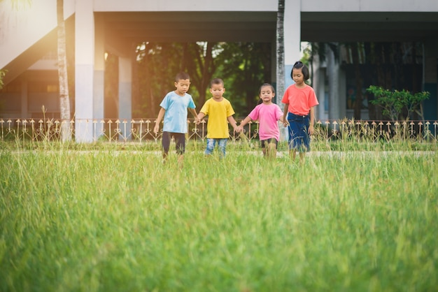 Gruppe asiatisches kinderhändchenhalten und auf rasenfläche in der schule zusammen laufen oder gehen