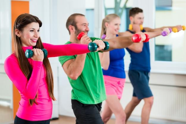 Gruppe athleten in der turnhalle gymnastik mit dummköpfen tuend