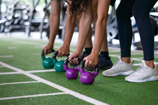 Gruppe athletisches trainingstraining des jungen mannes und der frau und übung mit kettlebell belasten am eignungsturnhallensportverein
