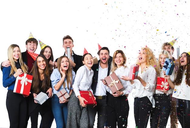 Gruppe attraktiver junger freunde, die über weißem hintergrund stehen. konzept des urlaubs.