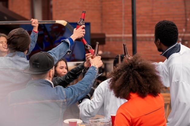 Gruppe aufgeregter eishockeyfans, die nach dem anschauen der spielübertragung mit bierflaschen klirren, während sie den sieg ihrer mannschaft feiern