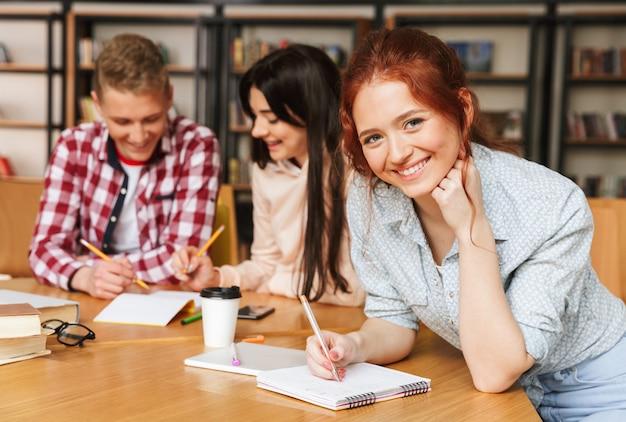 Gruppe aufgeregter teenager, die hausaufgaben machen