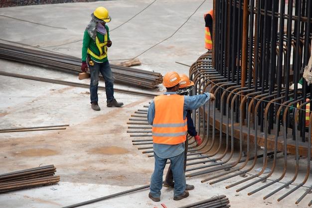 Gruppe bauarbeiterinstallationsstahl-wieder-stange an der großen grundlage