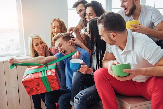 Gruppe beste freunde an der party. lächelnd und fröhliche menschen sitzen auf der treppe eine tasse kaffee begrüßen den geburtstag, tolles geschenk