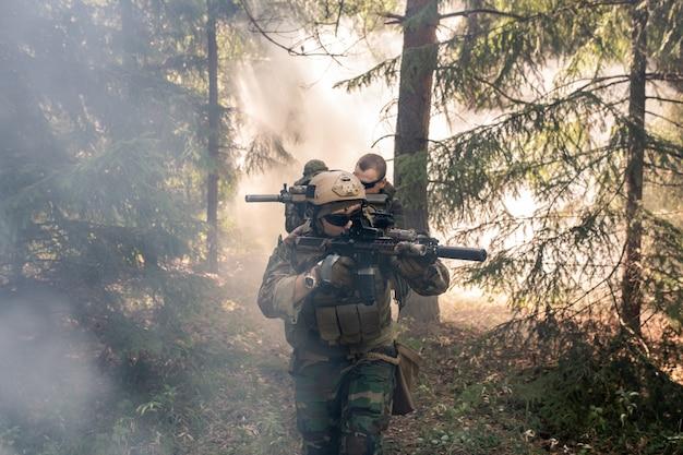 Gruppe bewaffneter soldaten in tarnkleidung, die gewehre hält und durch den nebligen wald kommt
