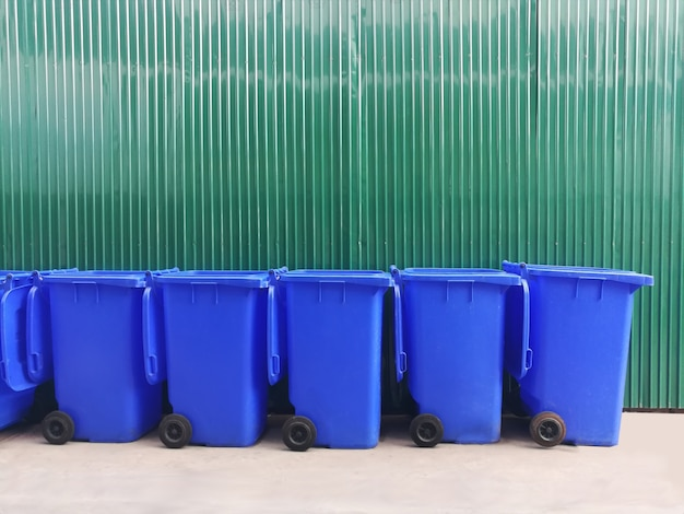 Gruppe blauer mülleimer auf zementboden mit grüner metallwand