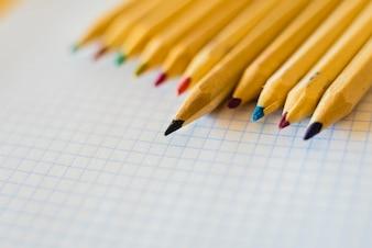 Gruppe Bleistifte angeordnet auf Millimeterpapier.