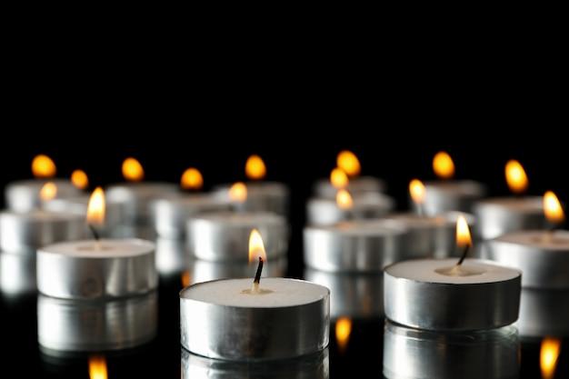 Gruppe brennender kerzen auf schwarz