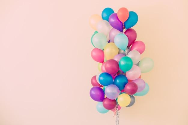 Gruppe bunte ballone auf pastellfarbhintergrund.