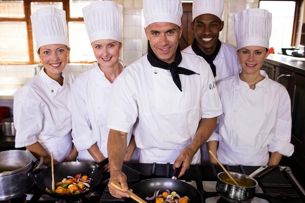 Gruppe chefs, die lebensmittel in der küche zubereiten