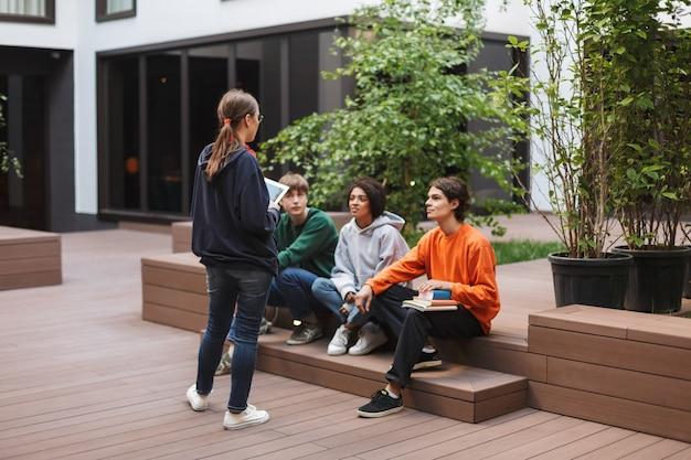 Gruppe cooler studenten, die sitzen und sich auf den unterricht vorbereiten, während sie zusammen im hof der universität studieren