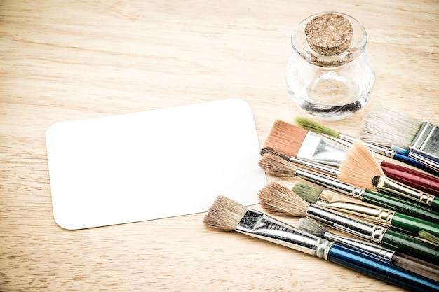 Gruppe der aquarellbürste und der leeren weißbuchkarte auf hölzerner tabelle