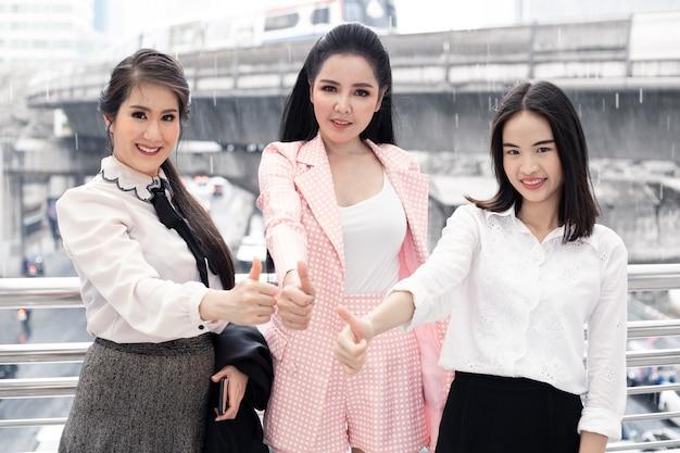 Gruppe der asiatischen geschäftsfrau daumen hoch mit einem lächeln im freien in der stadt. konzept der teamarbeit asiatische frau. thailändische büroangestelltegruppe.