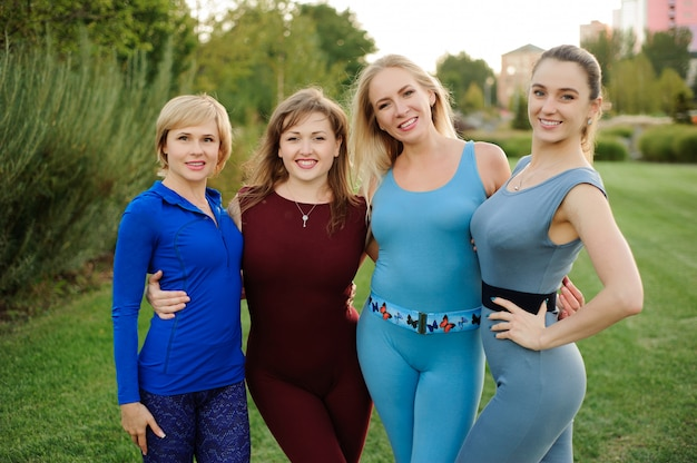 Gruppe der erwachsenen frau, die nach yoga draußen in einem park sich entspannt