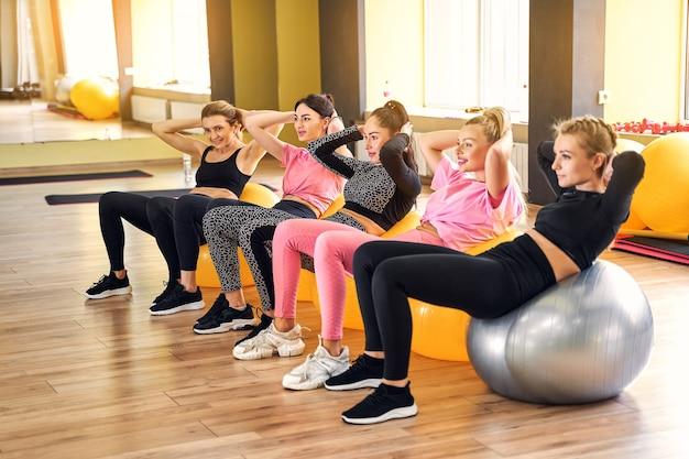 Gruppe der frau, die übung auf fitnessball tut