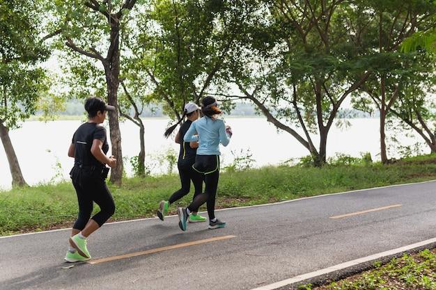 Gruppe der frauenübung morgens laufend auf parkspur.