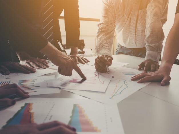 Gruppe der geschäftsmannsitzung analysieren die unternehmensleistung und das wachstum, die mit informationsdatenpapier unternehmen sind.