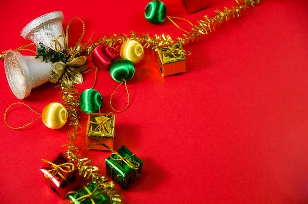 Gruppe der glocke, des balls und des geschenks im weihnachten auf rotem hintergrund auf draufsicht