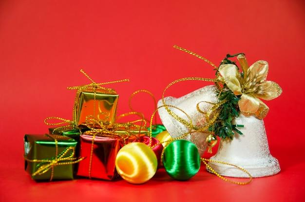 Gruppe der glocke und des geschenks im weihnachten auf rotem hintergrund