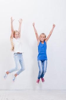 Gruppe der glücklichen jungen mädchen, die auf weiß springen