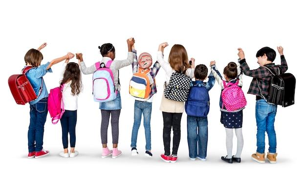 Gruppe der hinteren ansicht von den verschiedenen kindern, die in folge holdinghände in der luft stehen