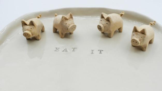 Gruppe der hölzernen schweinskulptur auf leerem teller, text